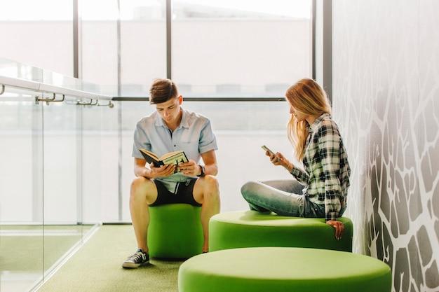 Jugendliche mit buch und telefon