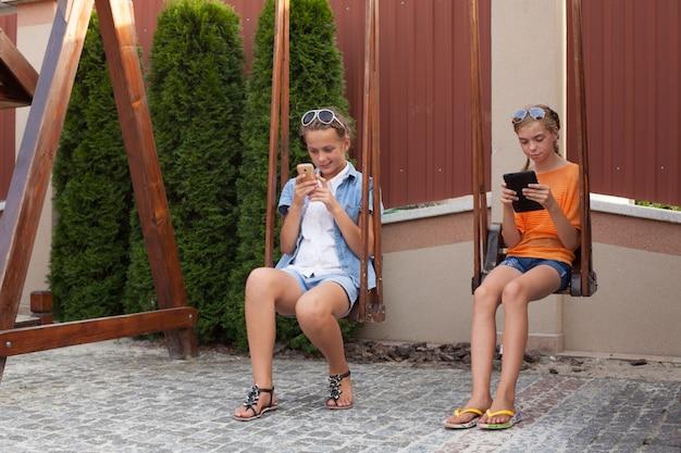 Jugendliche mit gadgets sitzen auf der schaukel
