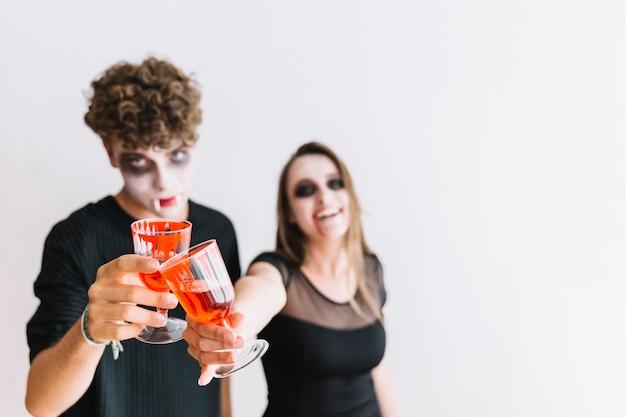 Jugendliche mit grimmigen klirrenden roten gläsern halloweens