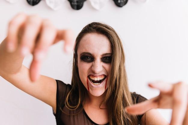 Jugendliche mit halloween-make-up, das furchtsames gesicht macht