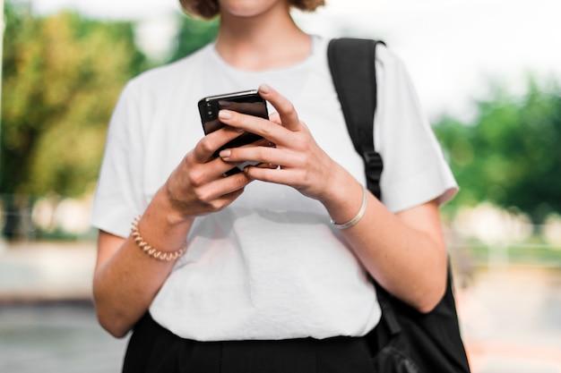 Jugendliche mit schulrucksack und telefon auf dem campus nach studien unter verwendung des telefons