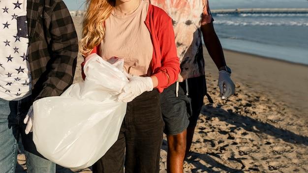 Jugendliche säubern strand, sammeln müll auf freiwilligenarbeit