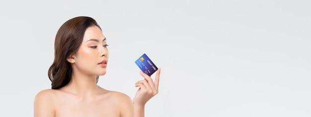 Jugendliche schöne asiatische frau, die kreditkarte zeigt