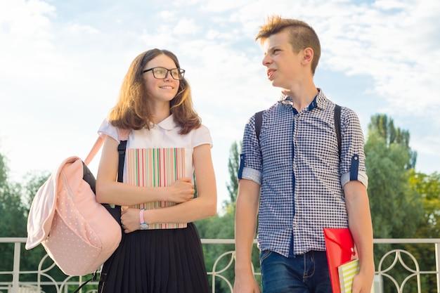 Jugendliche schüler mit rucksäcken, lehrbüchern gehen zur schule