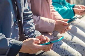 Jugendliche spielen Spiele, schreiben Text auf Telefone. Junge Leute halten die Smartphones, die O sitzen