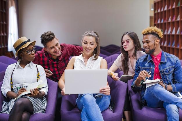 Jugendliche studieren mit laptop in der bibliothek