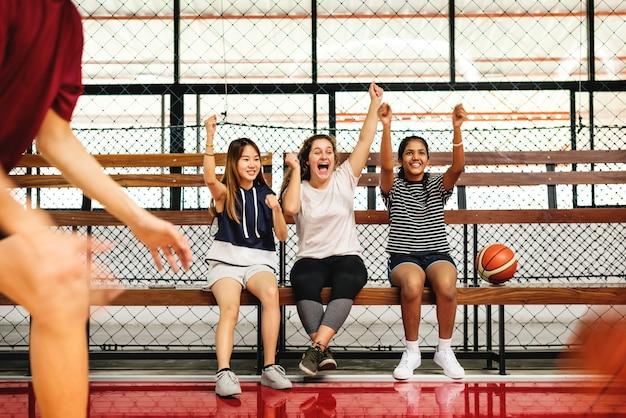 Jugendlichen, die den jungen zujubeln, die basketball spielen