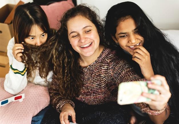Jugendlichen, die einen smartphone verwenden, um ein selfie in einem schlafzimmertreffpunkt und in einem freundschaftskonzept zu nehmen