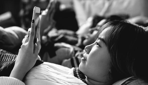 Jugendlichen, die smartphones auf einem bettinternet in der pyjamaparty verwenden