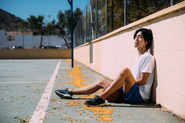 Jugendlicher, der am basketballplatz sich entspannt