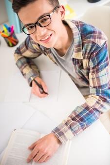 Jugendlicher, der am tisch sitzt und zu hause hausarbeit tut.