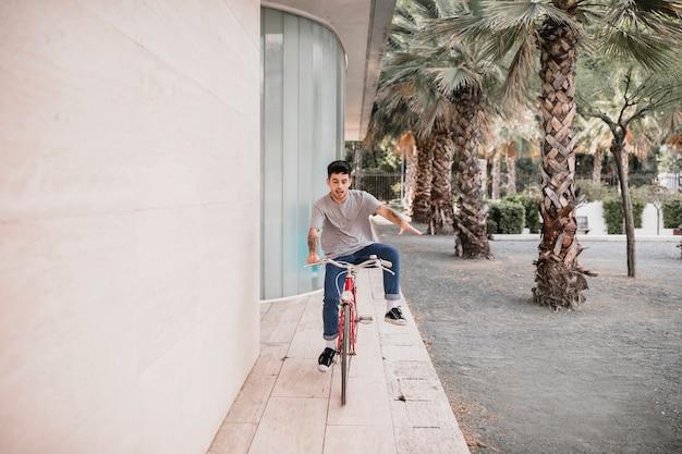 Jugendlicher, der auf fahrrad sich balanciert