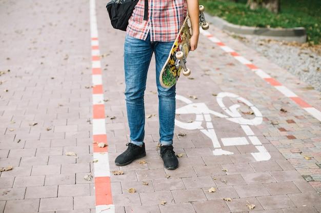 Jugendlicher, der auf fahrradweg mit skateboard steht