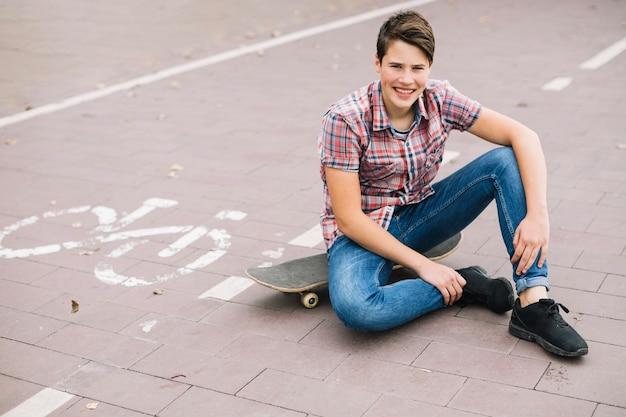 Jugendlicher, der auf skateboard nahe fahrradweg sitzt