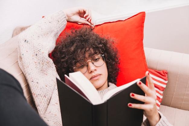 Jugendlicher, der auf sofa liest