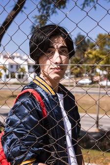 Jugendlicher, der durch zaun in der stadt schaut