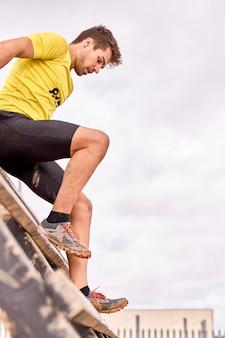 Jugendlicher, der einen hindernislauf in einem spartanischen rennen durchläuft