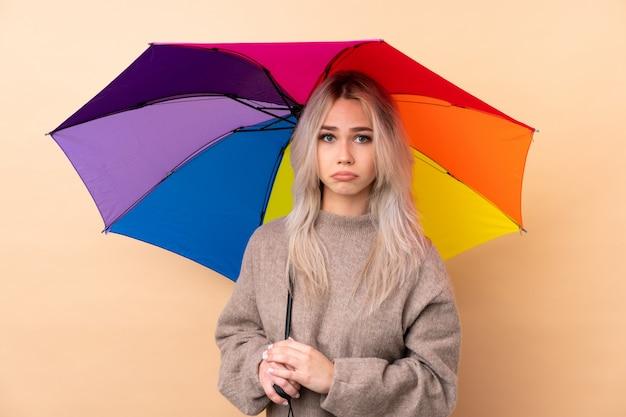 Jugendlicher, der einen regenschirm traurig hält