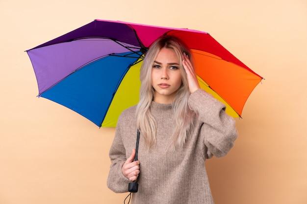 Jugendlicher, der einen regenschirm unglücklich und mit etwas frustriert hält. negativer gesichtsausdruck