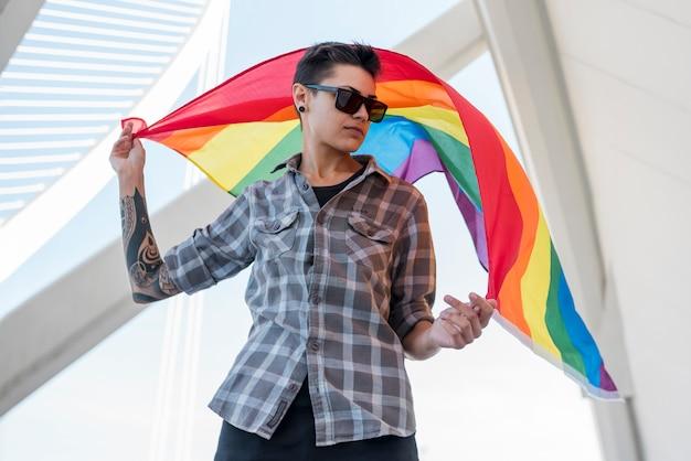 Jugendlicher, der flatternde regenbogenflagge hält