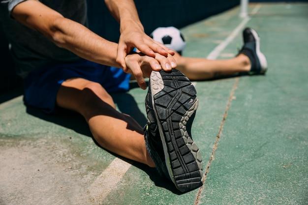 Jugendlicher, der fuß im fußballplatz ausdehnt