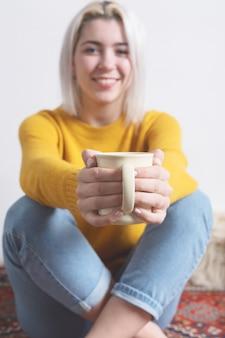 Jugendlicher, der ihnen eine tasse tee anbietet