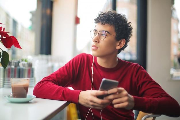 Jugendlicher, der in einer bar sitzt, musik hört und heiße schokolade trinkt