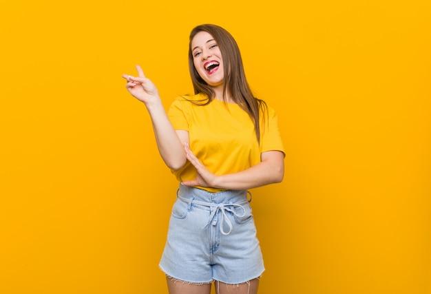 Jugendlicher der jungen frau, der ein gelbes hemd froh und sorglos zeigt ein friedenssymbol mit den fingern trägt.