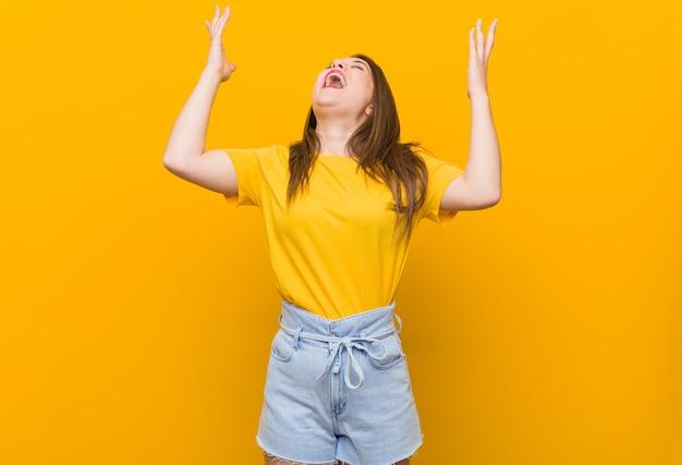 Jugendlicher der jungen frau, der ein gelbes hemd schreit zum himmel trägt und oben schaut, frustriert.