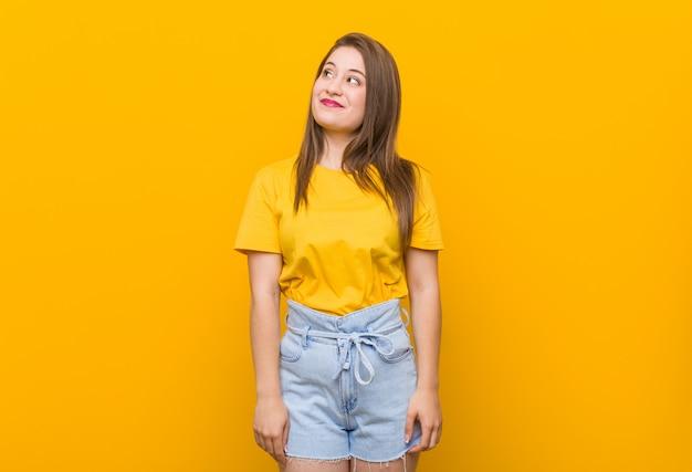 Jugendlicher der jungen frau, der ein gelbes hemd träumt vom erreichen von zielen und von zwecken trägt