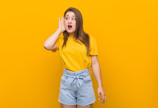 Jugendlicher der jungen frau, der ein gelbes hemd versucht, einen klatsch zu hören trägt.