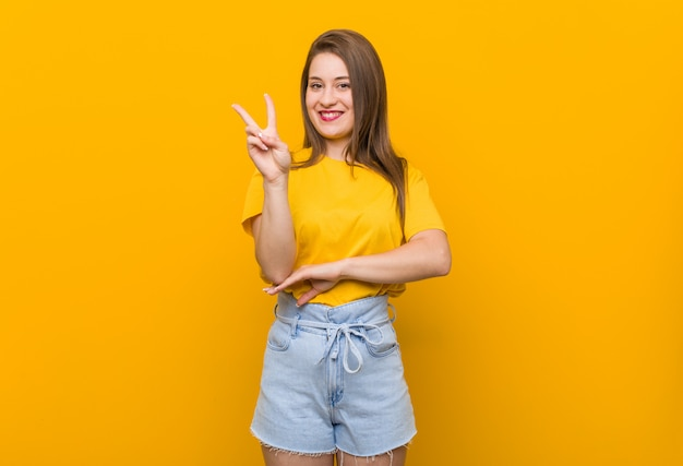 Jugendlicher der jungen frau, der ein gelbes hemd zeigt nummer zwei mit den fingern trägt.