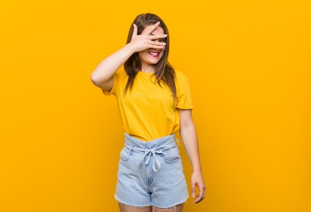 Jugendlicher der jungen frau, der ein gelbes hemdblinken durch finger, verlegenes bedeckungsgesicht trägt.