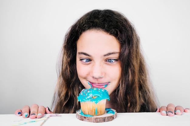 Jugendlicher, der lippen leckt, nachdem er muffin gegessen hat