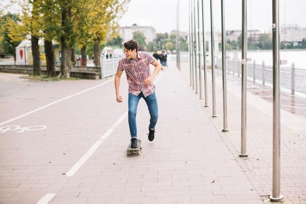 Jugendlicher, der nahe fahrradweg skateboard fährt