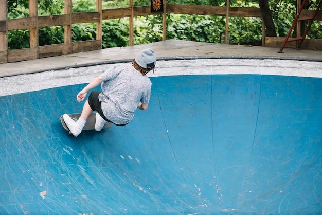 Jugendlicher, der nahe rand der schüssel skateboarding ist