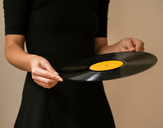 Jugendlicher, der retro- vinylsatz hält