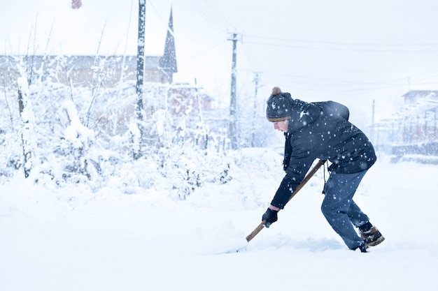Jugendlicher, der schnee mit einer schaufel im winter entfernt