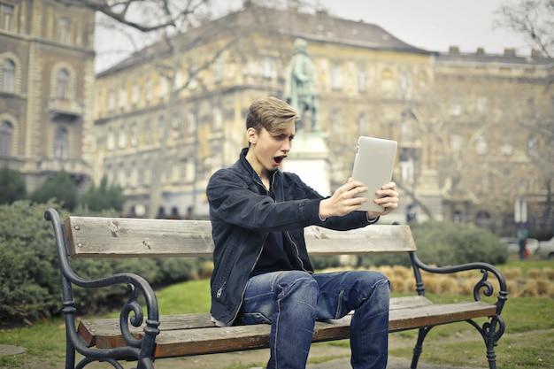 Jugendlicher, der sein tablet aufpasst