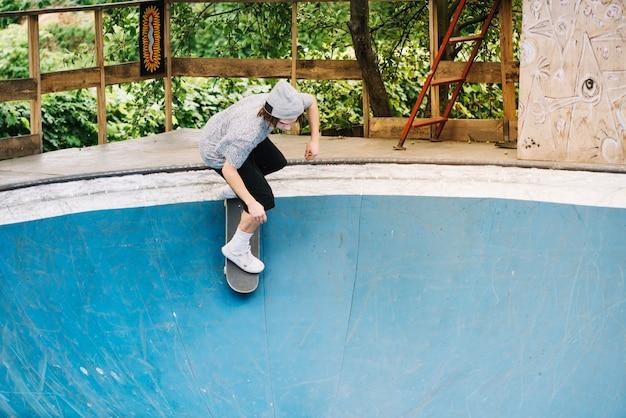 Jugendlicher, der skateboard hinunter rampe reitet