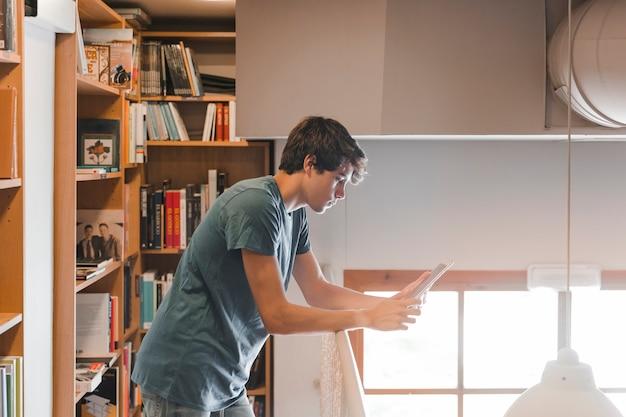 Jugendlicher, der tablette nahe geländer in der bibliothek verwendet