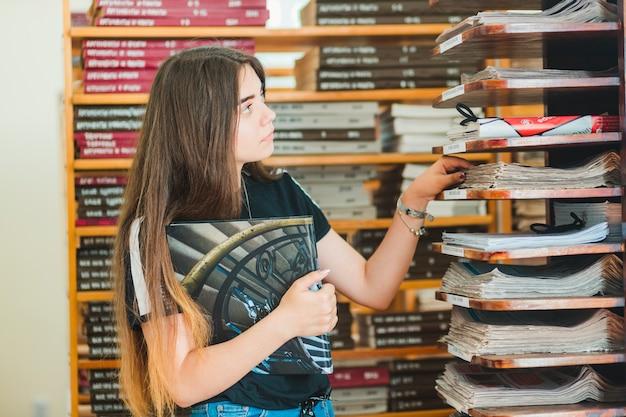 Jugendlicher, der zeitungen in der bibliothek betrachtet