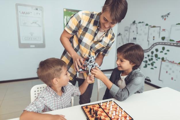 Jugendlicher, der zwei sitzenden jungen roboter zeigt.