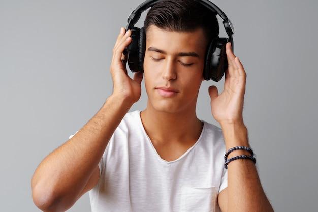 Jugendlicher des jungen mannes, der musik mit seinen kopfhörern hört