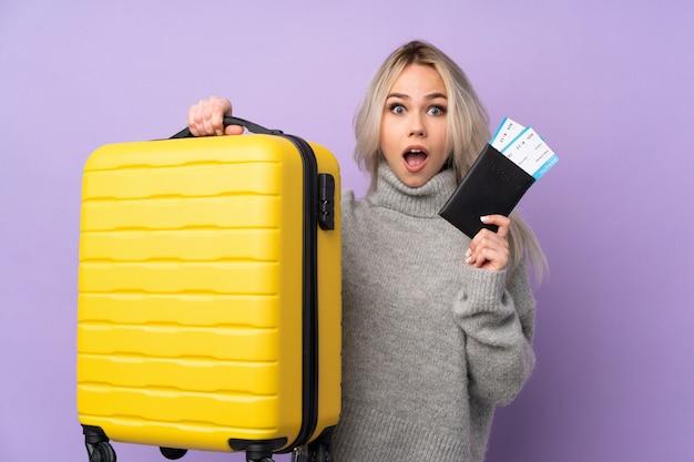 Jugendlicher in den ferien mit koffer und pass und überrascht