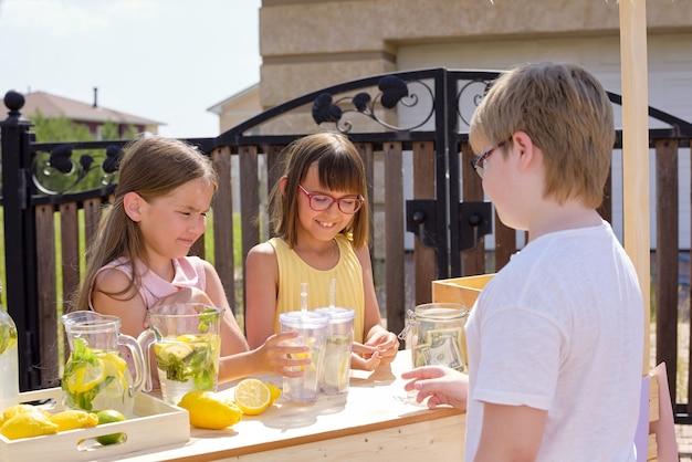 Jugendlicher junge, der glas der frischen kühlen limonade kauft, die von zwei entzückenden mädchen vorbereitet wird, die durch hölzernen stall stehen und getränke verkaufen
