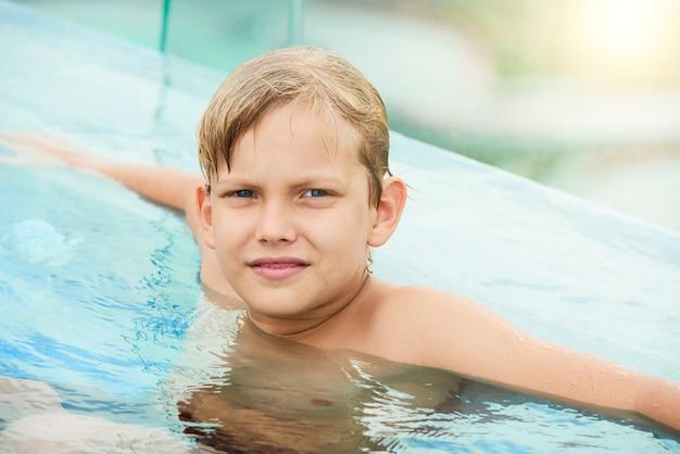 Jugendlicher junge, der im swimmingpool stillsteht