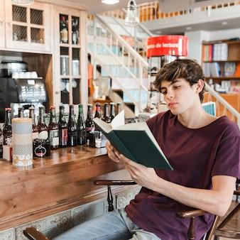 Jugendlicher mit dem buch, das im cafee sich entspannt