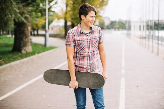 Jugendlicher mit dem skateboard, das auf fahrradweg steht