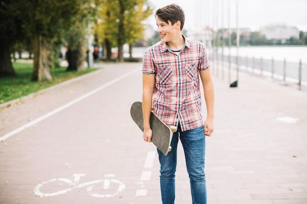 Jugendlicher mit dem skateboard, das nahen fahrradweg steht